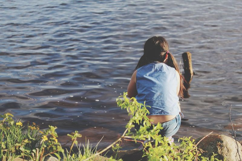 Rear view of girl crouching at shore