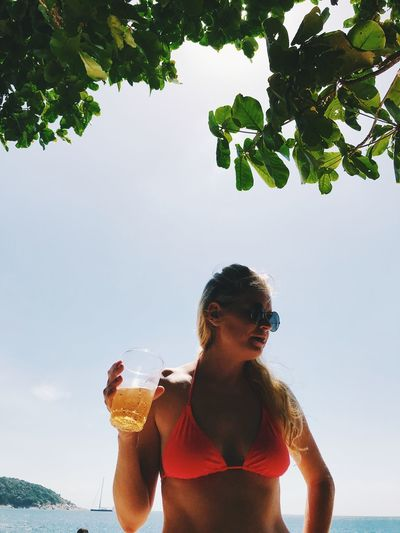 Woman wearing bikini holding drink while standing at beach against sky