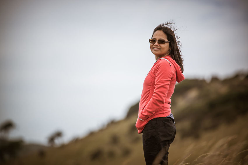 Asian woman standing in a New Zealand pasture, looking at camera Asian  Exercise Farm Field Grass Jumper Looking At Camera New Zealand Pasture Standing Sweater Wind Woman
