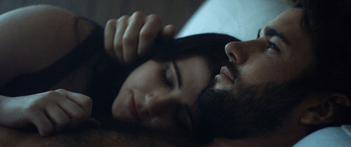 Close-Up Of Thoughtful Man Lying With Girlfriend On Bed