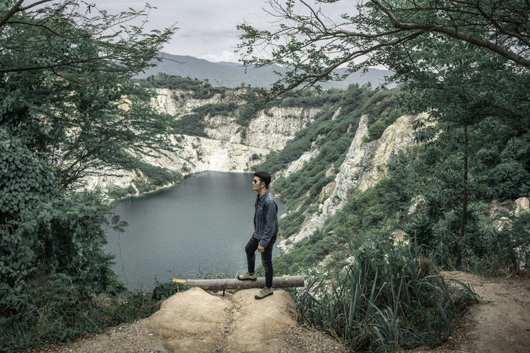 Man standing on mountain against trees