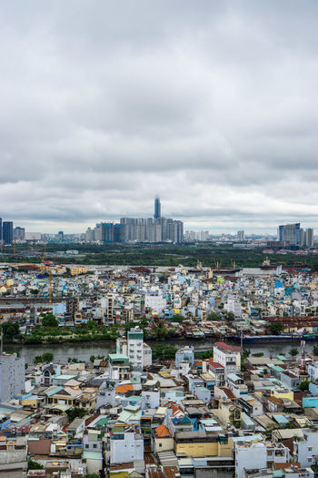 High angle view of buildings in city against cloudy sky
