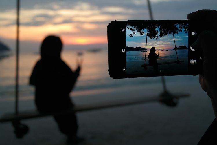 Rear view of silhouette people photographing sea against sky during sunset