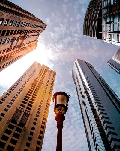 Low Angle View Of Lamp Post By Buildings Against Sky