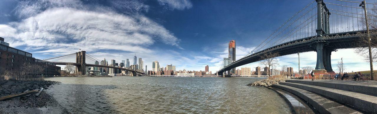 Suspension bridge over river against sky in city