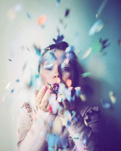 Portrait Of Mid Adult Woman Blowing Confetti