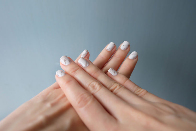 Close-up of woman with nail art against wall