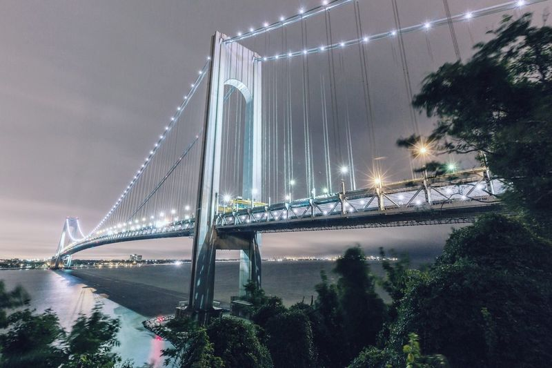 Low angle view of illuminated verrazano–narrows bridge at dusk