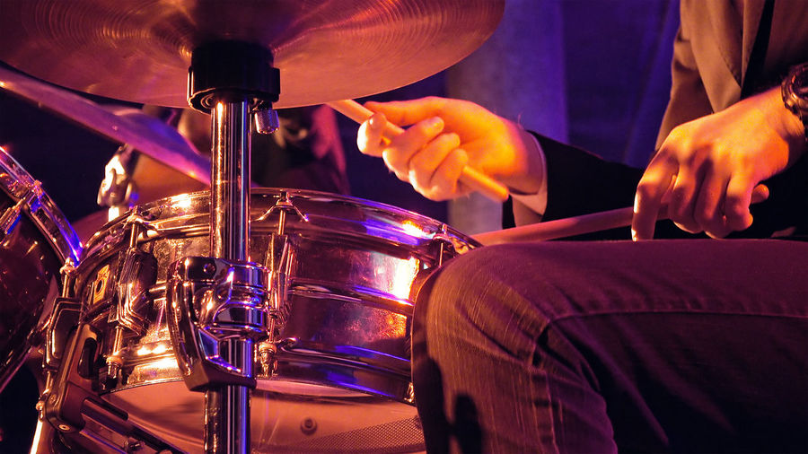 Midsection Of Man Playing Drum During Music Concert