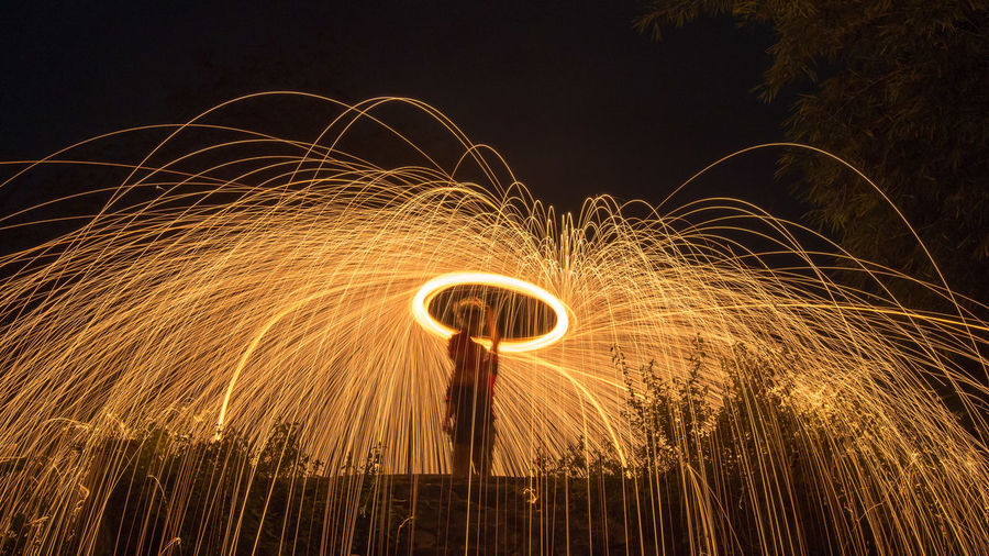 Person spinning illuminated wire wool at night