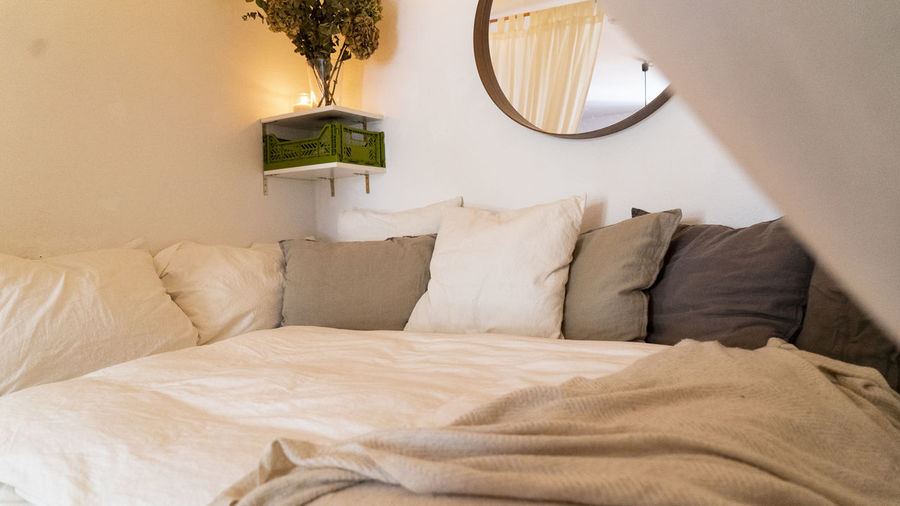 Cushions arranged on bed at home