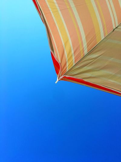 Cropped parasol against clear blue sky