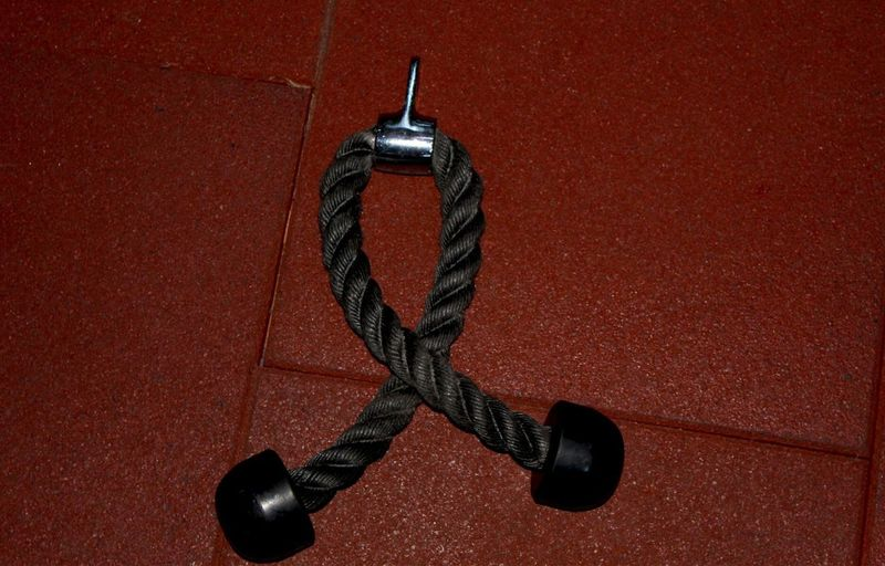 High angle view of metal hanging on rope against red background