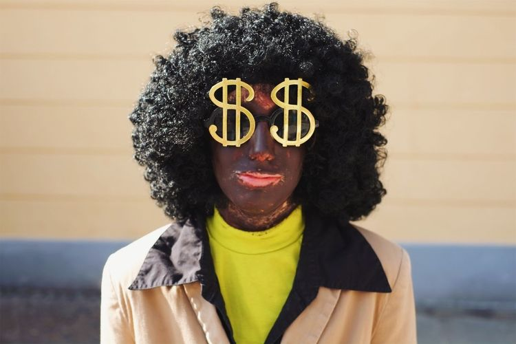 Portrait of woman wearing sunglasses with dollar sign