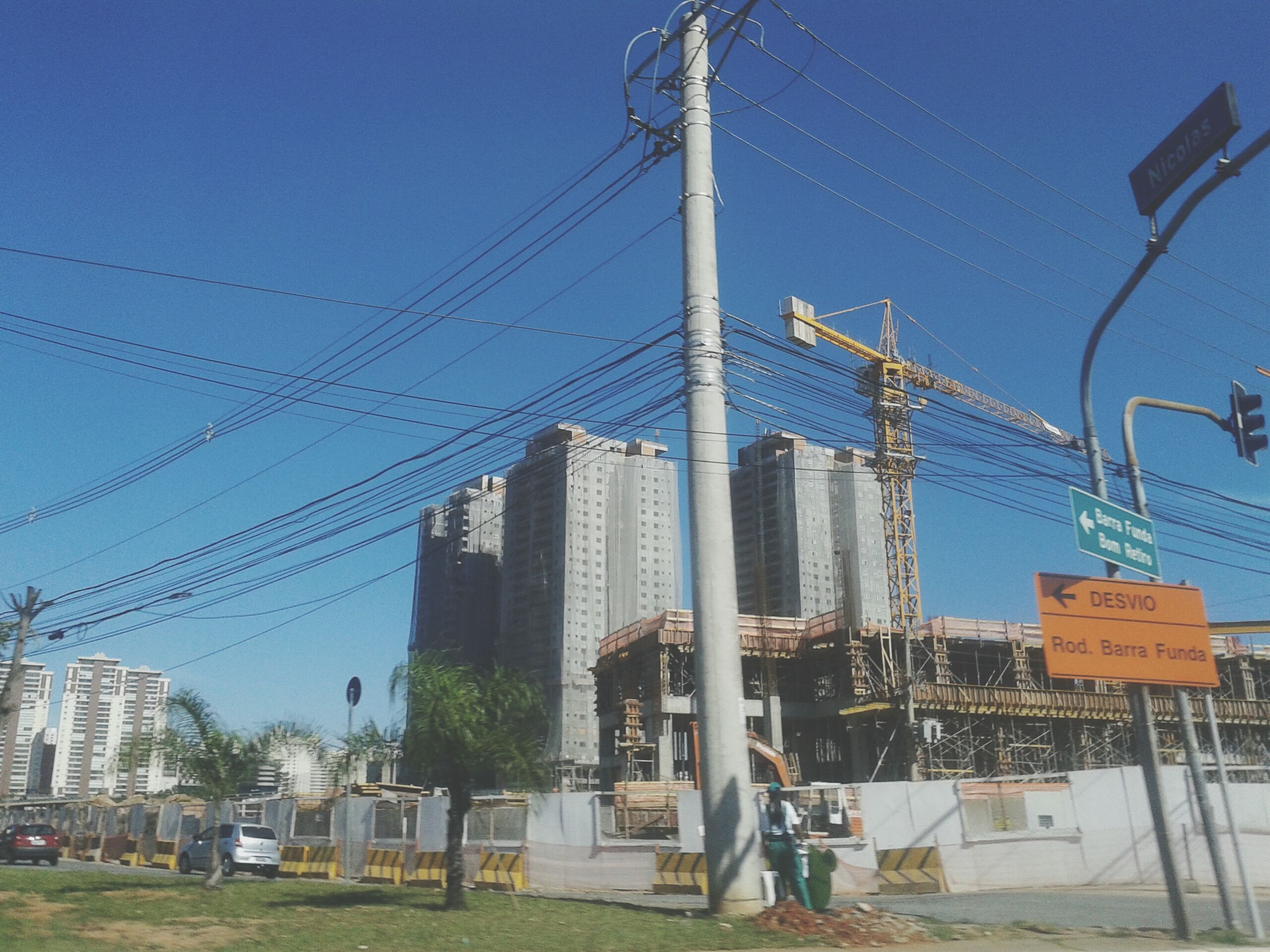 building exterior, built structure, architecture, blue, power line, clear sky, city, electricity pylon, sky, cable, electricity, construction site, sunlight, low angle view, fuel and power generation, power supply, transportation, day, outdoors, development