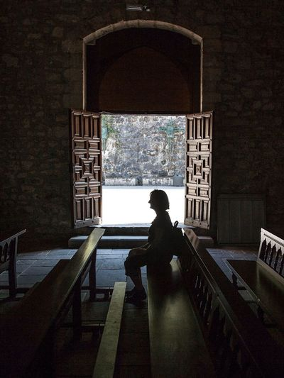Side view of woman sitting on bench in church