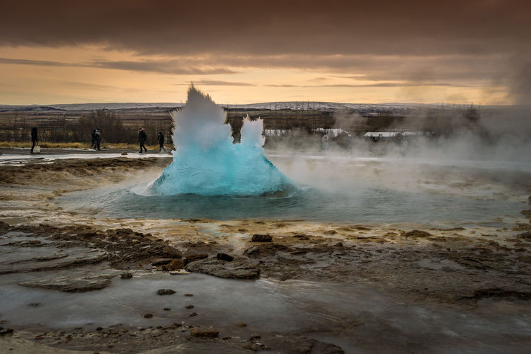 A geyser violently erupting just before the water leaps into the air