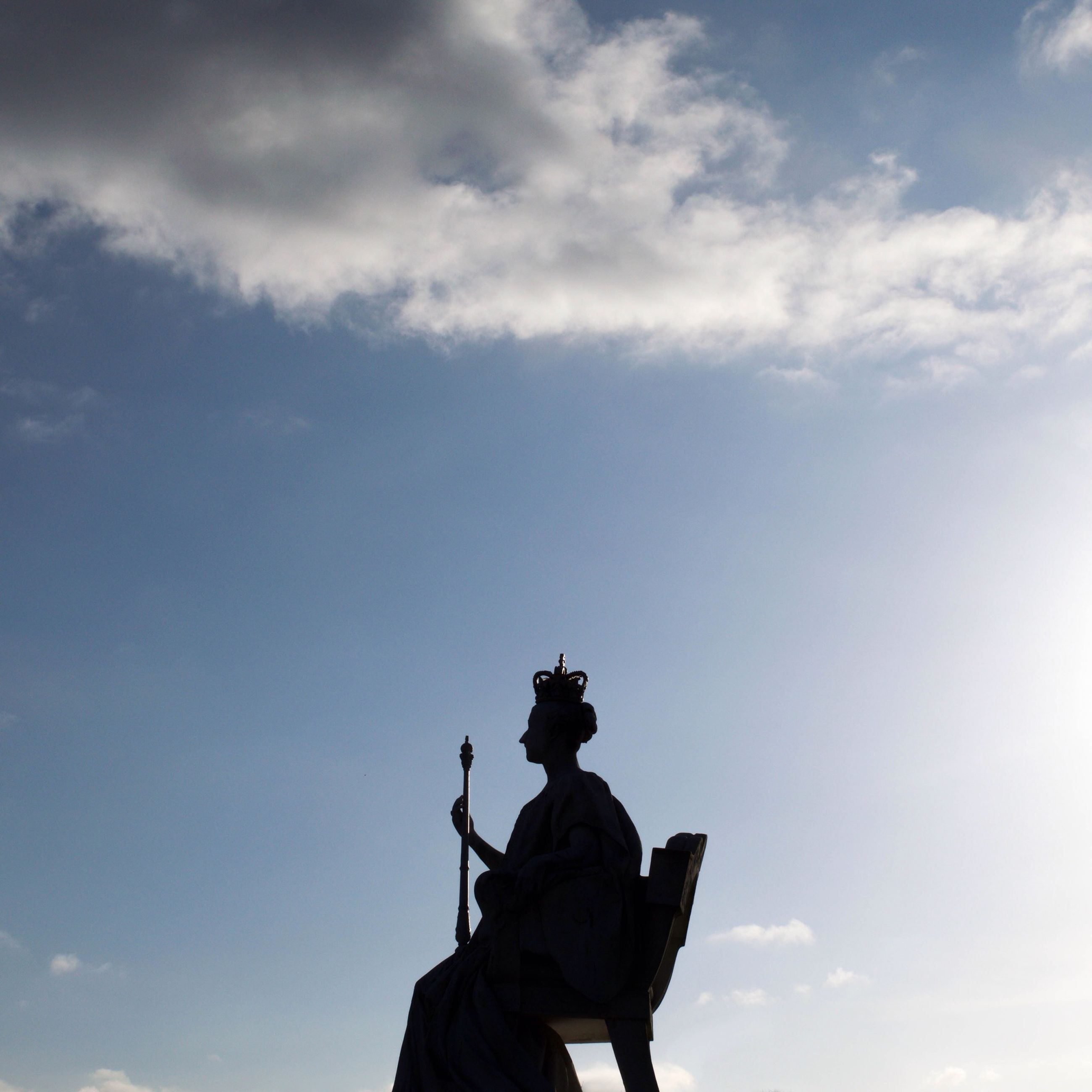 low angle view, sky, human representation, statue, cloud - sky, sculpture, standing, men, lifestyles, leisure activity, cloud, art and craft, silhouette, outdoors, rear view, art, day