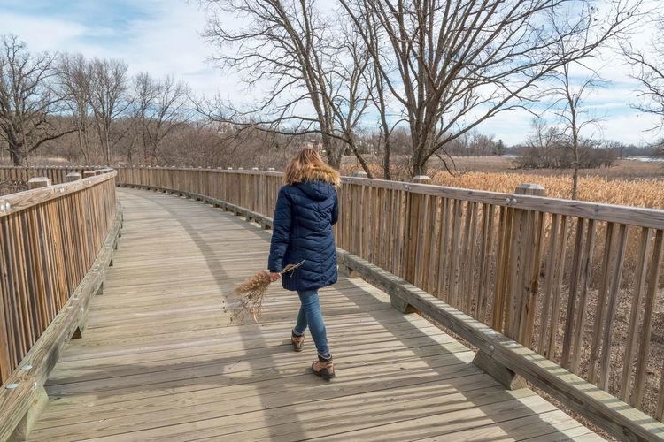 Rear view of girl walking on footbridge