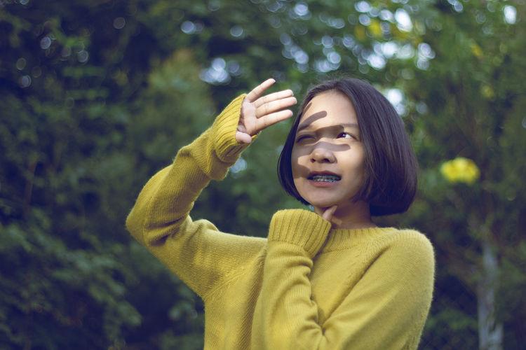 Teenage girl shield eyes against trees