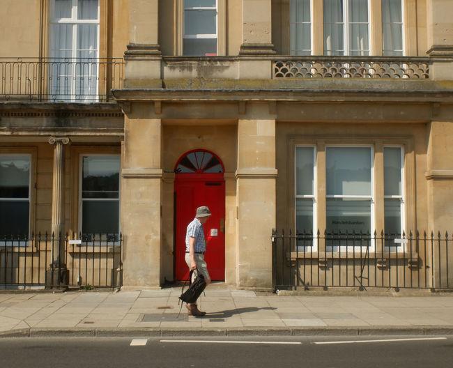 Full length side view of man walking on street against building