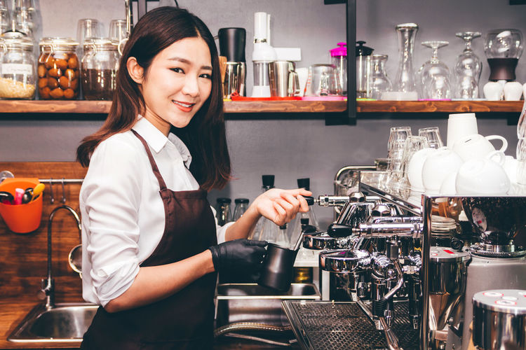 Women Barista using coffee machine for making coffee in the cafe Adult Bar - Drink Establishment Bar Counter Barista Business Cafe Coffee Maker Coffee Shop Drink Food And Drink Glass Hairstyle Indoors  Looking At Camera Making Occupation Portrait Preparation  Real People Refreshment Service Smiling Women Young Adult