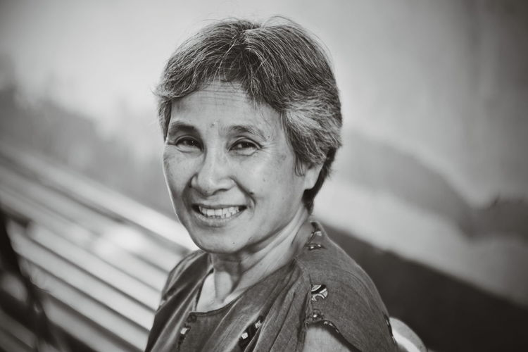 Close-up portrait of smiling senior woman against wall