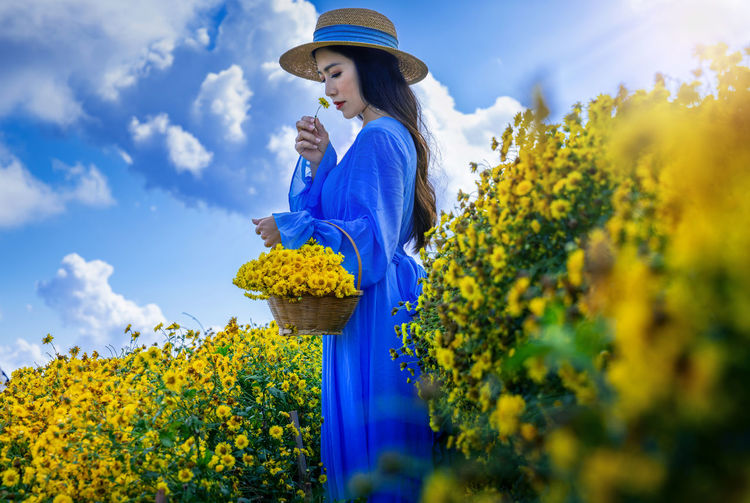 Full length of woman standing by sunflower against sky