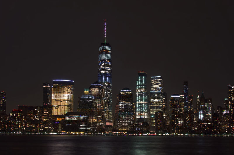 Illuminated one world trade center by hudson river in city at night