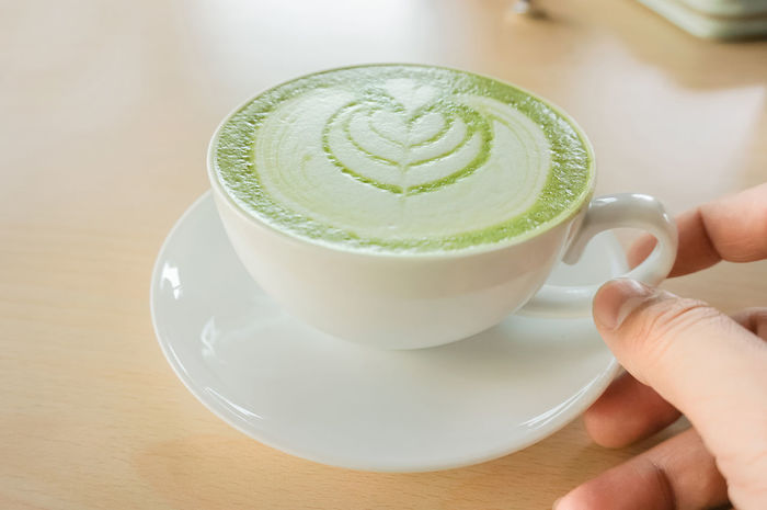 Coffee Holiday Recreation  Close-up Coffee - Drink Coffee Break Coffee Cup Drink Food And Drink Freshness Froth Art Frothy Drink Green Tea Healthy Eating Holding Human Body Part Human Hand Indoors  Lifestyles Mutcha People Refreshment Relaxation Saucer Table