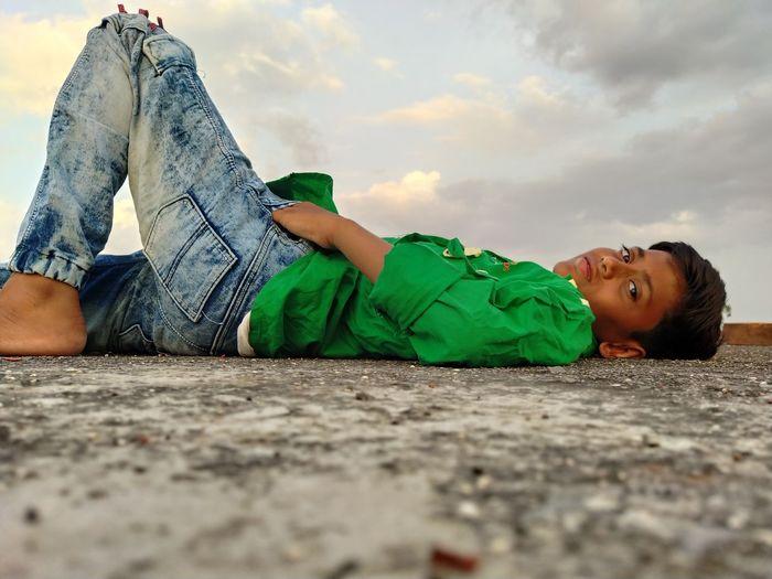 Portrait of boy lying on blanket against sky