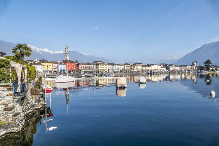 Panorama of ascona with houses with colorful facades reflecting on lake maggiore