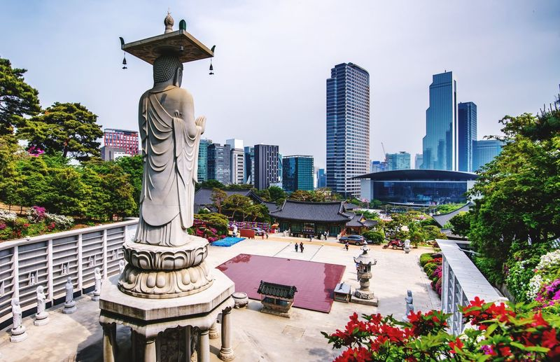 View of statue against buildings in city