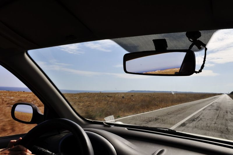 Close-Up Of Side-View Mirror Seen Through Car Window