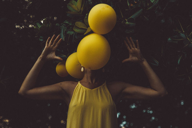 Woman with fruits over face on plants