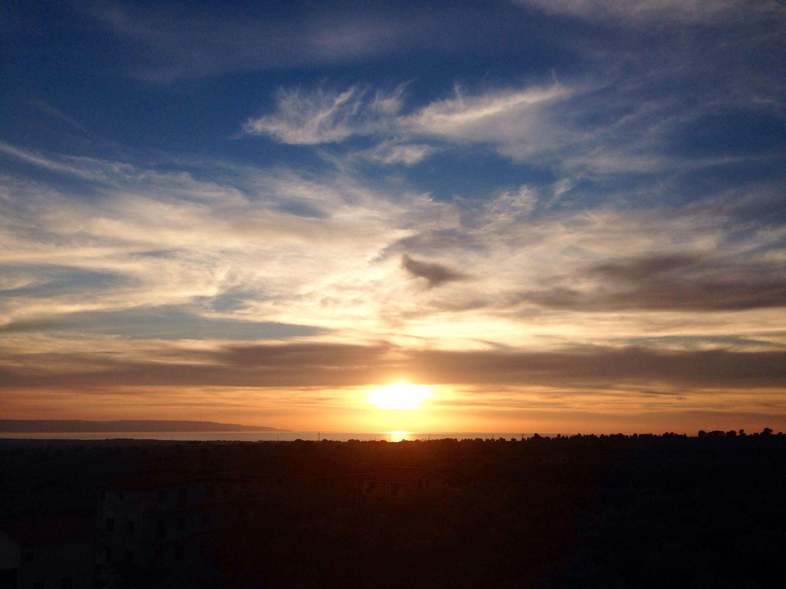 sunset, silhouette, sky, scenics, beauty in nature, tranquil scene, sun, cloud - sky, tranquility, orange color, landscape, nature, idyllic, cloud, sunlight, cloudy, dramatic sky, outdoors, sunbeam, moody sky