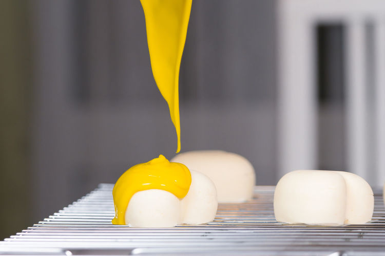 Close-up of cream over heart shape food on cooling rack