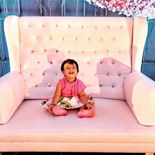 Full length portrait of cute baby girl sitting on sofa