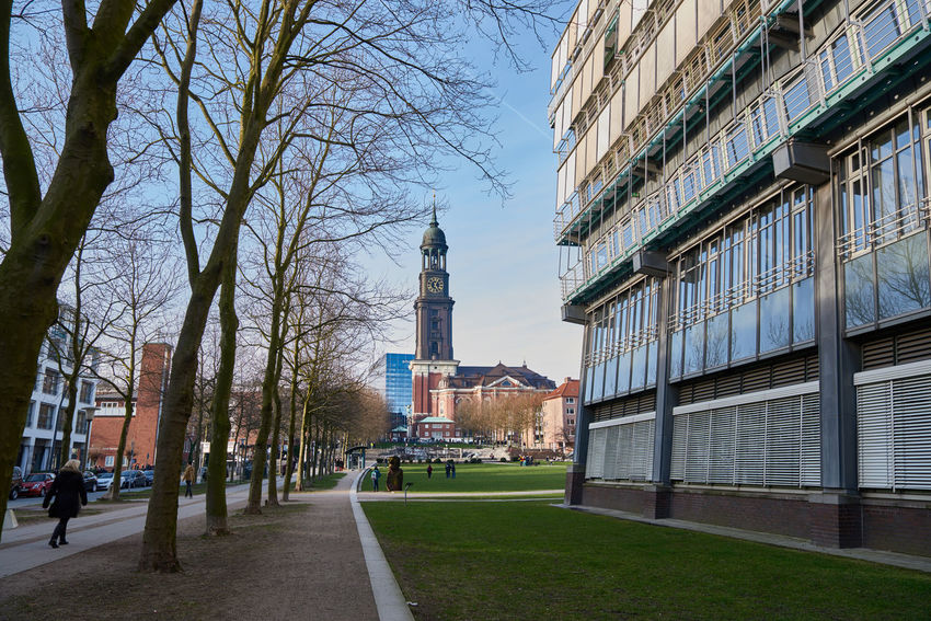 HAMBURG, GERMANY - MARCH 26, 2016: Unidentified individuals strolling along the headquarter building of media corporation Gruhner & Jahr - with view on the famous Michel Blue Sky City Destination Destinationwedding Gruhner & Jahr Hamburg Headquarter Headquarters Tourist Tranquility