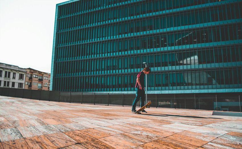 Full length of man skateboarding on building terrace