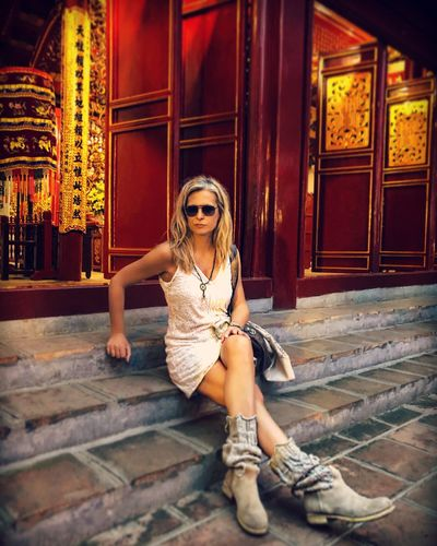 Full length portrait of woman sitting on steps at religious building