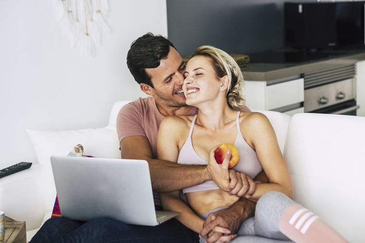 Cheerful and happy couple hugging and laughing at home lay down on the sofa - love and relationship concept with lifestyle healthy concept - technology and home working for young people Two People Sitting Togetherness Love Women Emotion Adult Connection Indoors  Young Adult Men Laptop Technology Couple - Relationship Computer Positive Emotion Wireless Technology Furniture Real People Young Women Using Laptop Eating Healthy Eating Lifestyles Kiss Complicity Hugging Domestic Room Inside Summer Natural Sofa Sitting Caucasian Casual Clothing