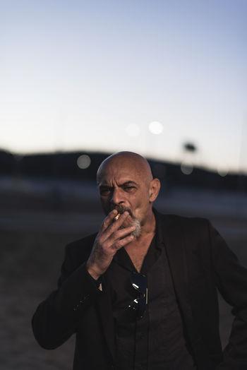 Portrait of bald businessman smoking cigarette against sky during sunset