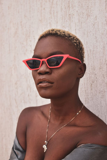 Close-up of young woman wearing sunglasses standing against wall