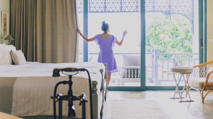 Rear view of woman standing on bed at home