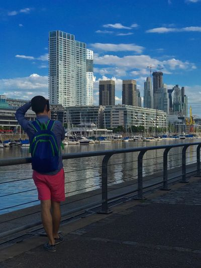 Rear View Of Man Standing By Railing Against Urban Skyline