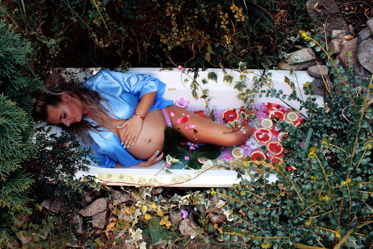 High angle view of pregnant woman lying in bathtub amidst plants