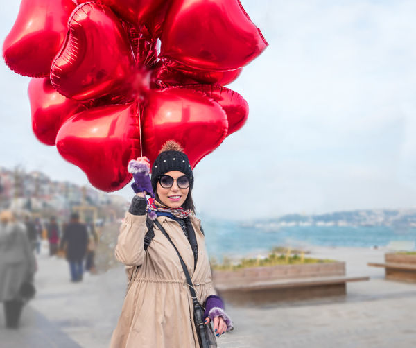 Portrait of woman with red balloons standing on street