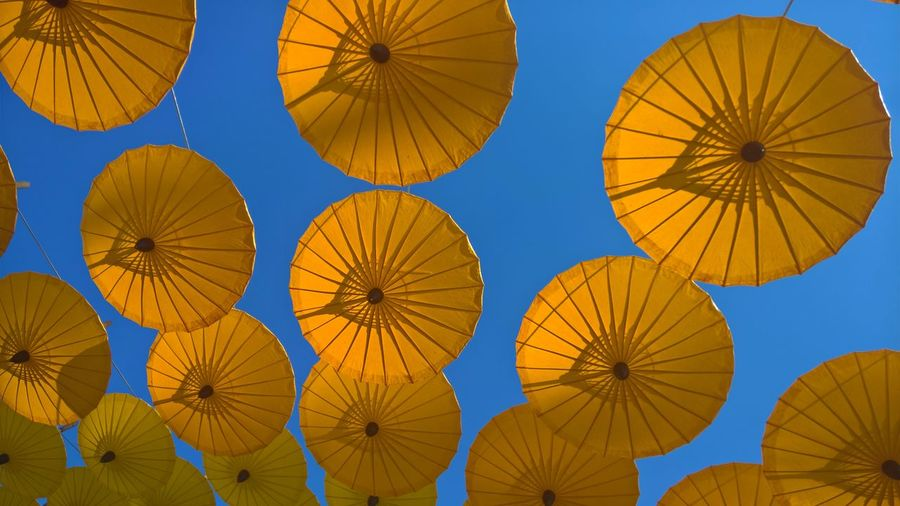 Low angle view of yellow umbrellas hanging against clear blue sky