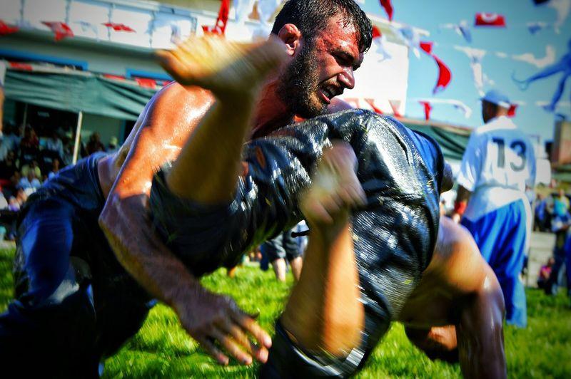 Men wrestling on field during festival